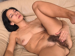 Eva is a naturally hairy woman, with small natural breasts, petite frame and hairy pussy. She sits in her favorite couch and strips her pants and shirt off, before beginning to rub her pussy.